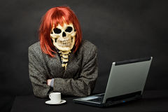 Man dressed as death sits at table with computer Royalty Free Stock Image