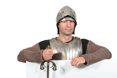 Man dressed as a knight. With a board left blank for your message Stock Photo