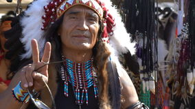 A man dressed as Native American Indians next to his shop souvenirs. Slow motion stock video