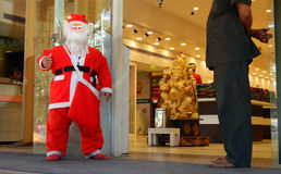 Man Dressed as Santa claus stand in front of clothes store wishing people Stock Photo