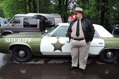 A man dressed as sheriff stands by an old car royalty free stock image