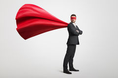 Man dressed as a superhero. Serious businessman dressed as a superhero in red mask and cloak over light grey background Stock Image