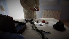 Man dressed with bathrobe in a hotel talking on the phone next to a bed stock video footage