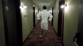 Man dressed in a bathrobe and slippers walking at the long hotel corridor. Back view stock video footage
