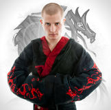 Man dressed in black dragon kimono demonstrating martial arts co. Mbat Stock Images