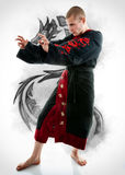 Man dressed in black dragon kimono demonstrating martial arts co. Mbat Royalty Free Stock Image