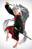 Man dressed in black dragon kimono demonstrating martial arts co. Mbat Stock Image