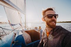 Man dressed in casual wear and sunglasses on a yacht. Happy adult bearded yachtsman close-up portrait. Handsome sailor. On a boat smiling during regata on a sea royalty free stock photo