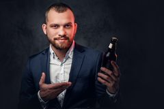 A man dressed in an elegant suit holds craft beer. Stock Photos