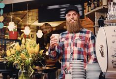 A man dressed in a fleece shirt posing at the counter in a coffee shop. Redhead bearded male dressed in a fleece shirt posing at the counter in a coffee shop stock image