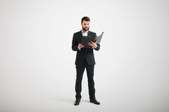 Man dressed in formal wear familiarize with materials in the fol Stock Photo