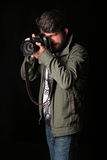 Man dressed in khaki jacket takes picture. Close up. Black background Royalty Free Stock Image