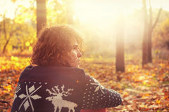Man dressed in knit sweater with deers sitting  on autumn leaves in park. Royalty Free Stock Image