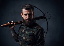 A man dressed in a military jacket holds crossbow. A tattooed, bearded hunter male dressed in a military jacket holds crossbow Royalty Free Stock Photography
