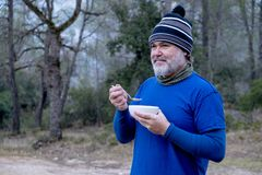Man dressed in mountain clothes and a woolen hat breakfast a bowl of cereal in the woods royalty free stock image