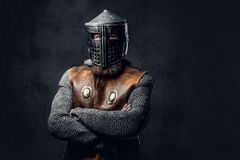A man dressed in Nordic armor. Studio portrait of a male Viking dressed in Nordic armor and an iron helmet over dark grey background Royalty Free Stock Photo