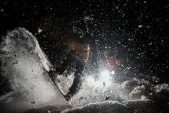 Man breathtakingly riding snowboard in the dark under the snow Royalty Free Stock Image