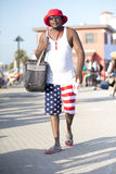 Man dressed in patriotic clothing walking along boardwalk. Black man walks along the boardwalk of Pensacola Beach on the 4th of July wearing sunglasses and a Royalty Free Stock Photos