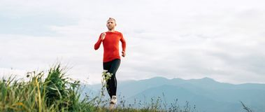 Man dressed in red long sleeve shirt runs by the road with mount stock photo