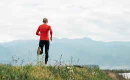 Man dressed in red long sleeve shirt runs by the road with mountain background wide angle shoot stock images