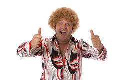 Groovy Attitude Seventies Guy. A man dressed in 70`s costume giving an excited thumbs up on a white background Stock Photo