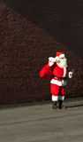 Man dressed in santa suit. In front of brick wall in a city Stock Photos