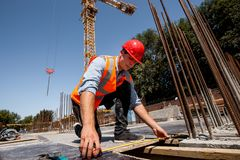 Man dressed in shirt, orange work vest and helmet measures the hole with a tape measure on the building site royalty free stock image
