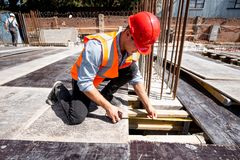 Man dressed in shirt, orange work vest and helmet measures the hole with a tape measure on the building site stock images