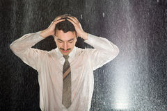 Businessman on the rain having headache Stock Photo