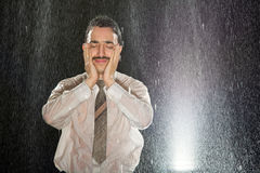 Businessman on the rain having headache Royalty Free Stock Image