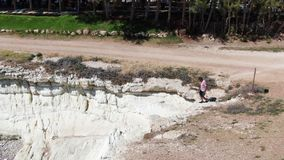 Man dressed in shorts, sneakers and a T-shirt walking along a cliff. Foamy waves hitting the rocky shore going down to. The water. Shooting from the drone stock video footage