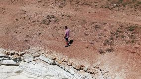 Man dressed in shorts, sneakers and a T-shirt walking along a cliff. Foamy waves hitting the rocky shore. Shooting from. The drone. Cyprus stock video