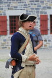 Man dressed in soldier's uniform,educating visitors on life during 1776,Fort Ticonderoga,New York,2014. Young soldier. walking visitors through the everyday life royalty free stock images