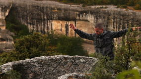 A man dressed in soldier uniform practices Qigong in the mountains. A man dressed in soldier uniform practices Qigong meditation practice in the mountains stock footage