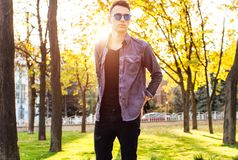 a man dressed in stylish clothes, sunglasses, walks in the park, stock photo