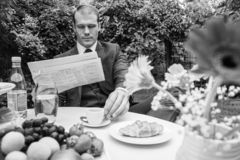 Man dressed in suit drinks esperesso at a cafe table. Handsome man dressed in vintage classical suit drinking coffee at cafe table while reading newspaper Royalty Free Stock Image