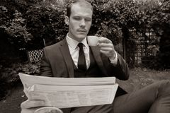 Man dressed in suit drinks esperesso at a cafe table. Handsome man dressed in vintage classical suit drinking coffee at cafe table while reading newspaper Stock Photo