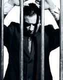 Man dressed in suit in jail behind prison bars Stock Photos