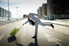 Man dressed in suit with a suitcase. Man dressed in suit and suitcase sitting on the floor in the street Royalty Free Stock Photos