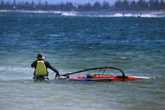 Windsurfer and his sail board stock photography