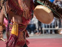 Man dressed in traditional Aztec garb beats on a drum during a m stock photos