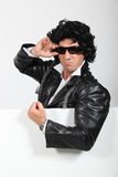 Man dressed up in a silly wig. And biker jacket standing with a board left blank for your image Stock Photos