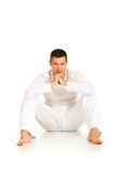 Man dressed in white sitting on the floor Stock Photo