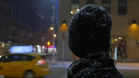 Man in Snowstorm Looks at Buildings on 5th Avenue in Manhattan. 7994 A man dressed for a winter snowstorm looks around at buildings on 5th Avenue in New York stock video