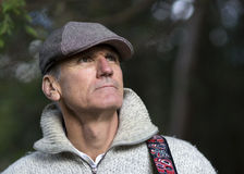 Man dressed in a wooly sweater and duckbill cap. Royalty Free Stock Image