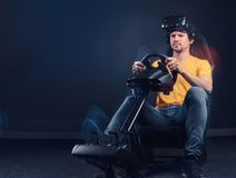 Man wearing VR headset driving on car racing simulator cockpit with seat and wheel. Man dressed in yellow shirt and jeans wearing VR headset driving on car royalty free stock photo