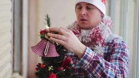 Man dresses beautiful little glowing Christmas tree stock footage