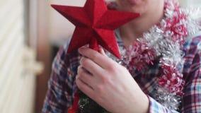 Man dresses beautiful little glowing Christmas tree stock video footage