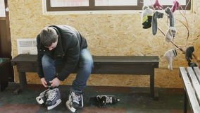 Man dresses hockey skates for ice skating in locker room. Male with dark hair in jeans, black jacket ties up long shoelaces. Preparation of footwear for winter stock video footage