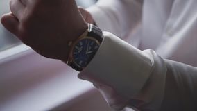 A man dresses a watch on his arm standing in front of the window. Close-up stock video